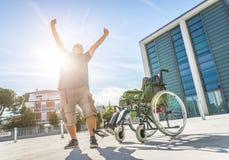 L'homme a obtenu son miracle capable tenir après son frome de blessure le fauteuil roulant Photos libres de droits