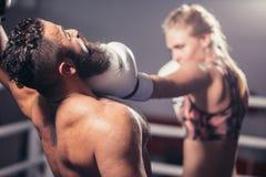 L'homme obtiennent de frapper par le boxeur de femme en anneau Photos stock