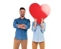 L'homme occasionnel de sourire se tenant avec des mains a croisé près de son amant Photo stock