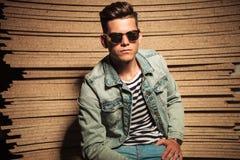 L'homme occasionnel frais sérieux utilisant des lunettes de soleil et s'assied Images stock