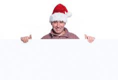L'homme occasionnel mûr dans le chapeau de Santa tient un grand conseil vide Image stock