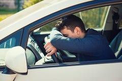 L'homme occasionnel presque de sommeil maintient la main et la tête sur le volant étant attente fatiguée dans l'embouteillage apr images stock