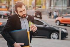 L'homme occupé est pressé, il n'a pas le temps, il va manger le casse-croûte sur l'aller Travailleur mangeant, café potable photos stock