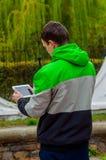 L'homme par temps d'automne a trouvé WI fi et a plaisir à observer les actualités Photos libres de droits