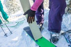 L'homme parasitaire installe le camus de colle sur des skis, en montagnes sauvages de neige images libres de droits