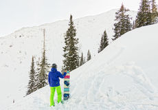 L'homme parasitaire se tient sur le flanc de montagne dans un casque et des WI Photo libre de droits