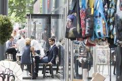 L'homme parle à une femme s'asseyant à une table en café Images libres de droits