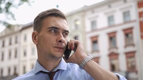 L'homme parle au téléphone se tenant sur la rue banque de vidéos