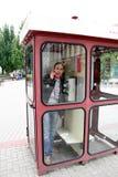 L'homme parle par le téléphone dans une cabine téléphonique Photographie stock libre de droits