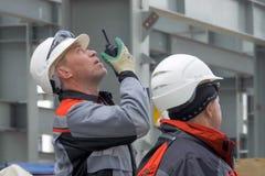 L'homme parle sur la radio Travailleur de l'usine Travailleur dans un casque photographie stock libre de droits