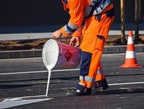 L'homme peint des panneaux routiers sur l'asphalte Image libre de droits
