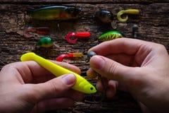 L'homme perce l'amorce de crochet pour pêcher sur la table Photos libres de droits