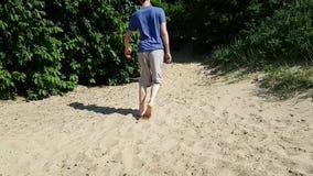 L'homme peut à peine marcher sur le sable avec ses pieds nus La vue du dos claudication Promenade-traitement d'une personne banque de vidéos