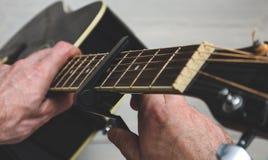 L'homme place le capo sur la guitare photographie stock libre de droits