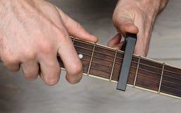 L'homme place le capo sur la guitare images libres de droits
