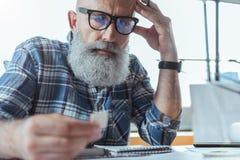 L'homme plus âgé élégant songeur travaille sur le projet Photo libre de droits