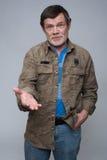 L'homme plus âgé avec la barbe grise montre sur quelque chose Photo stock