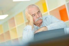 L'homme plus âgé avec la main sur le temple a le mal de tête Photo stock