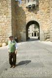 L'homme plus âgé bien habillé avec le chapeau marche par la porte de la ville murée, Avila Espagne, un vieux village espagnol cas Photo stock