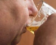 L'homme plus âgé boit de la bière de la tasse en verre, plan rapproché photographie stock