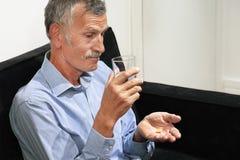 L'homme plus âgé boit une pilule de douleur images stock