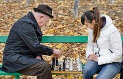 L'homme plus âgé discutant pendant une partie d'échecs avec la femme s'asseyent ensemble sur un banc de parc en bois Photo libre de droits