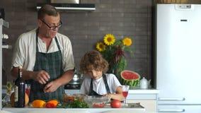 L'homme plus âgé donne au garçon un couteau de cuisine et t'enseigne comment couper un concombre Grand-père et petit-fils dans la clips vidéos