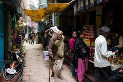 L'homme plus âgé se penche sur une canne sur une rue Images stock