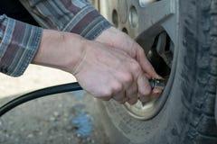 L'homme pompe la roue de voiture image stock