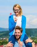 L'homme porte l'amie sur des épaules, fond de ciel Concept romantique de date La femme tient le coeur sur le symbole de bâton de  Photos libres de droits