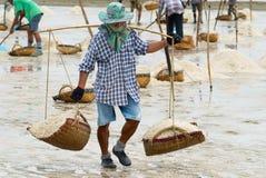 L'homme porte le sel à la ferme de sel dans Huahin, Thaïlande Image libre de droits