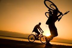 L'homme porte une bicyclette au coucher du soleil image libre de droits