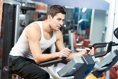 L'homme positif aux pattes vont à vélo la machine d'exercices Image stock