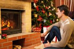 L'homme près de la cheminée dans Noël a décoré la maison photographie stock