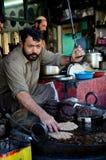 L'homme prépare le plat pakistanais de viande de chiche-kebab de chapli sur la poêle Gilgit Pakistan Image libre de droits