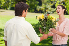 L'homme présente son ami avec des fleurs Photographie stock libre de droits