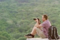 L'homme prend des photos d'une colline à l'arrière-plan de la forêt Image stock