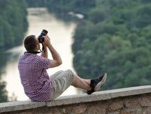 L'homme prend des photos d'une colline à l'arrière-plan de la forêt et de la rivière Photos stock