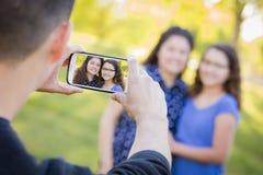 L'homme prend la photo de téléphone portable de l'épouse et de la fille Image stock