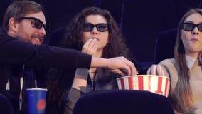 L'homme prend le maïs éclaté du seau à la salle de cinéma Image libre de droits