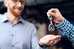 L'homme prend sa voiture du service automatique Le mécanicien vire les clés de voiture sur le client image stock