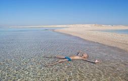 l'homme prend un bain de soleil se situer dans l'eau Images libres de droits