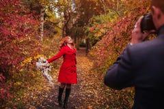 L'homme prend une photo de son amie dans la forêt d'automne Photographie stock libre de droits