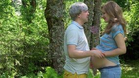 L'homme principal gris apportent la fleur de l'ail pour son baiser de femme enceinte et ventre de caresse clips vidéos
