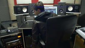 L'homme produit la musique électronique dans le projet et met en marche l'équipement dans un studio producteur clips vidéos