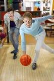 L'homme projette la bille dans le bowling ; l'ami supporte le sien Photo libre de droits