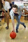 L'homme projette la bille dans le bowling ; la femme regarde l'homme Image stock