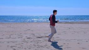 L'homme pulse sur le coureur actif sain de débutant d'ajustement de mode de vie de plage de sable de mer clips vidéos