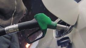 L'homme réapprovisionne en combustible l'automobile sur la station d'essence au plan rapproché de chutes de neige clips vidéos