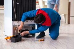 L'homme réparant le réfrigérateur avec le client photographie stock
